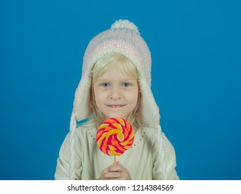 A sweet tooth. Little girl hold lollipop on stick. Little child with sweet lollipop. Happy candy girl. Happy childhood food.