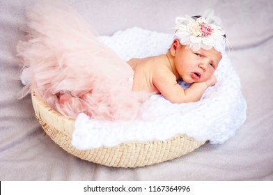 A sweet unhappy to be awaken newborn infant baby girl. A surprised and upset look. A tiny newborn girl in a soft basket studio portrait. Head flower bow on her head.