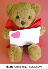 Sweet Valentines Day teddy bear with big red bow holding heart-decorated envelope with space for copy.