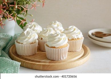 sweet vanilla cupcake with buttercream put on wooden board, image soft tone.
