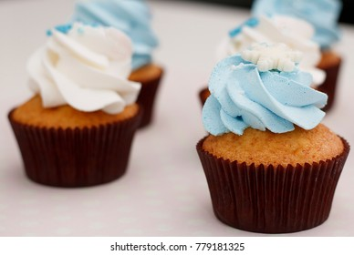 Sweet vanilla cupcakes with caramel filling and blue and white cheese cream, decorated with snowflakes and other delicious on colorful background.