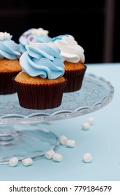 Sweet vanilla cupcakes with caramel filling and blue and white cheese cream, decorated with snowflakes,  marshmallow and other delicious on glass stands.