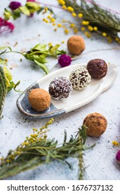 Sweet vegan protein cocoa chocolate oatmeal with dates, carob, coconut meat, sesame seeds and banana energy balls or bars. Healthy dessert. Truffles on plate