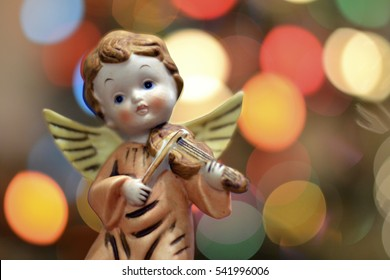 Sweet Vintage Angel Figurine in front of Blurry, Colorful Christmas Lights