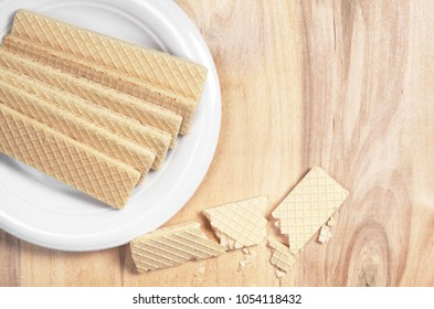 Sweet wafers in white plate on wooden table, top view with space for text