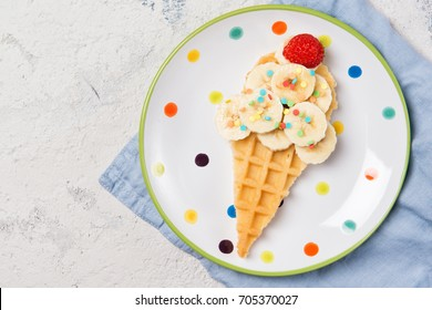 Sweet waffle with banana and strawberry in a shape of ice cream cone, food for kids idea, top view