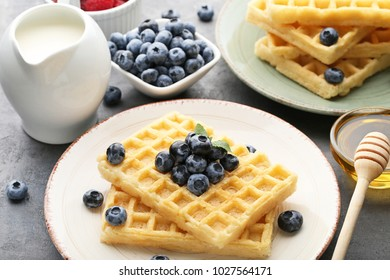 Sweet waffle with bluberries, milk and honey on grey wooden table