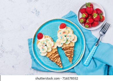 Sweet waffles with banana and strawberry in a shape of ice cream cone, meal for kids idea, top view