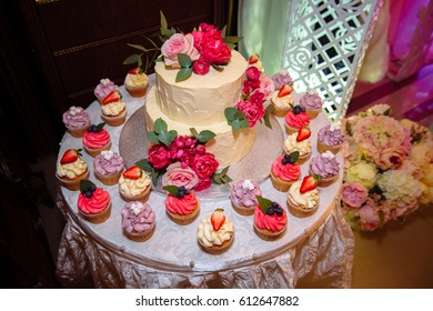 sweet wedding cake with candy bar, muffins, cakes and sweets in area of wedding party. Concept of advertising scenery of food and desserts