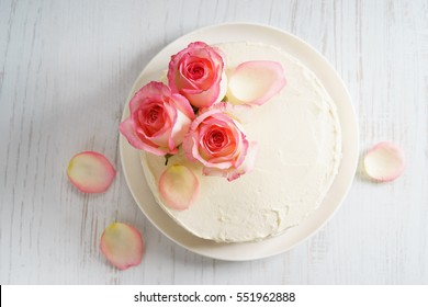 sweet white buttercream round cake with pink rose flowers on top, valentines love concept