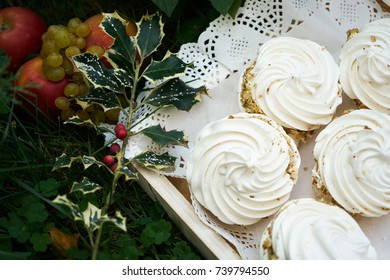 Sweet white meringue. Meringue tartlet cake and christmas decoration with fresh fruits and holly tree branch with red berries. Delicious homemade dessert meringue for xmas or new year.
