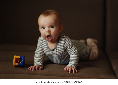 sweet yawning baby with toy on the sofa