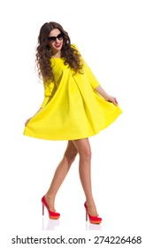 Sweet Yellow Dress. Beautiful fashion model in sunglasses walking in yellow dress and red high heels. Full length studio shot isolated on white.