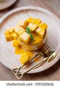 Sweet Yellow Mango dessert, cheesecake. Ripe yellow mango cheesecake serves on the round wooden tray with a small brass spoon and fork. Homemade sweets.