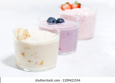 sweet yoghurts with fruits and berries on white table, closeup