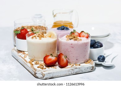 sweet yogurts with fruit and berries for a delicious breakfast on white table, horizontal