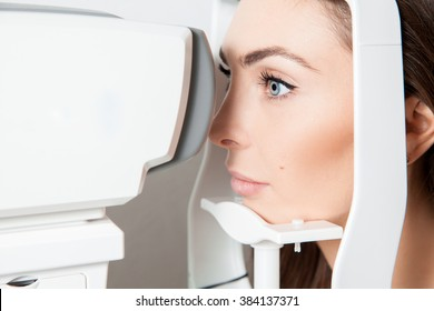 Sweet young adult brunette looking at eye test machine in ophthalmologist. Ophthalmologist. medical, health, ophthalmology concept