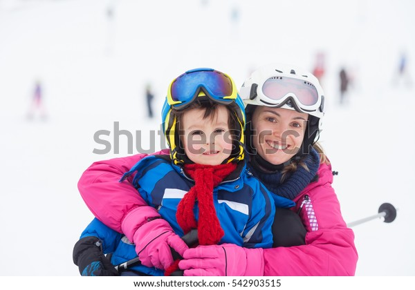Sweet young boy and his mother, learning to ski on a mild ski slope in Austrian ski resort on a cloudy day