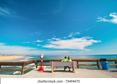 A sweet young couple sitting on a bench on the pier, looking out into the water