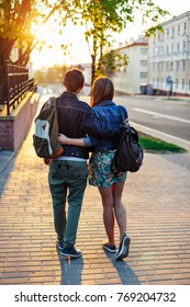 Sweet young couple standing back on the street in summer evening with backpacks travel style