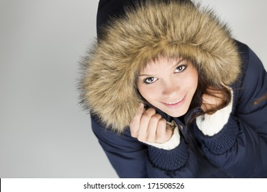 Sweet young girl in warm winter jacket with fur hood, looking up with a cute smile on her face, isolated on grey background.