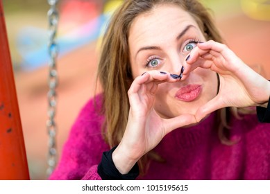 Sweet young woman holding fingers in a heart shape next to her eye, looking through a heart