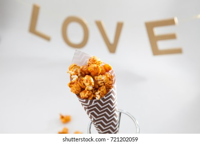 Sweetcorn in striped paper cone on support with love message behind