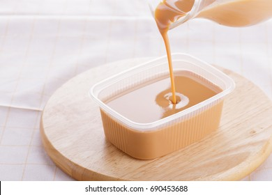 sweetened condensed milk on wooden background.