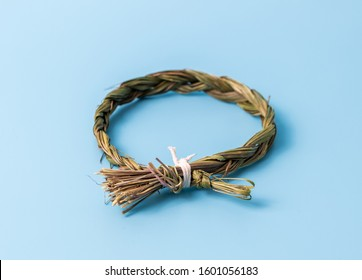 Sweetgrass braid tied with twine isolated on a blue background.