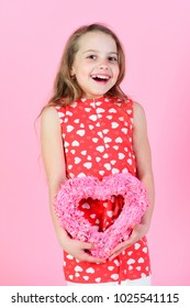 Sweetheart child with long hair smiling in red dress. Happy girl holding rosy heart on pink background. Romantic love concept. Valentine and valentines day celebration. Kindness and tenderness.