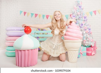 sweetheart plus size young girl sitting in a beige lingerie around the Christmas tree with a huge sweets on white background