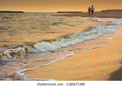 Sweetheart walking on the beech in the evenning while sunset.