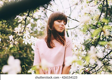 sweet,lovely girl standing on soft background Magnolia blossoming flowers,the wind blowing her hair,punched sun rays,it stands in white pink dress with her eyes closed and a small smile smiling tender