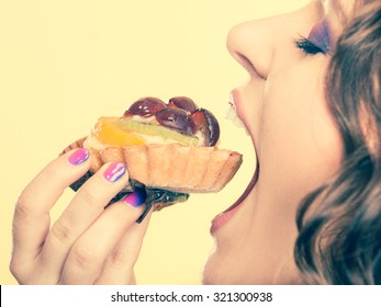 Sweetness and happiness concept. Closeup cute woman curly hair eating fruit cake cupcake face profile yellow background