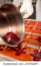 Sweets artisanal production of fruits loly pop at the factory. Close up of the saucepan pan with liquid hot red sugar dispensing to the orange mold. Artisanal production in France