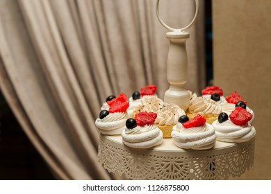 Sweets assortment/Arrangement of meringues with cream and berries and frosting cupcakes on a special tray.