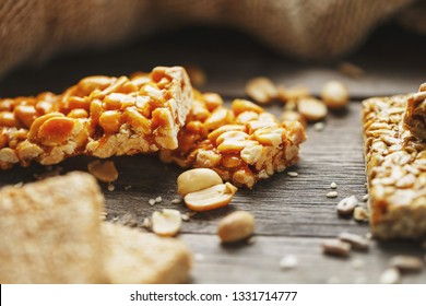 Sweets bar of peanuts on a vintage background with burlap. Delicious oriental sweets Gozinaki from sunflower seeds, sesame and peanuts, covered with honey with a shiny icing