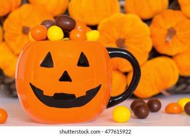 Sweets and candies in the mug. Pumpkin wreath background. Scary halloween.