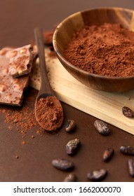 sweets, confectionery and culinary concept - chocolate with hazelnuts, cocoa beans and powder in wooden bowl with spoon on brown background