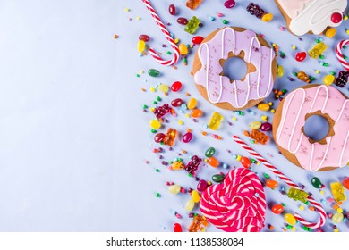 Sweets creative lay out, dessert concept with lollipops, jellies, candy, cookies donuts and cupcakes, bright yellow background top view copy space