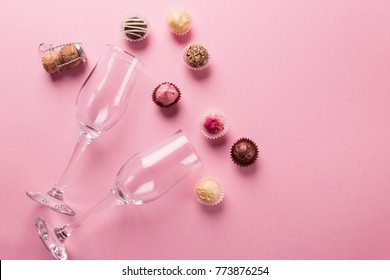 Sweets from dark and white chocolate and empty glasses on a pink background. Celebratory concept. Copy space. Top view of flat layout