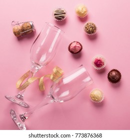 Sweets from dark and white chocolate and empty glasses on a pink background. Celebratory concept.  Top view of flat layout. Square frame