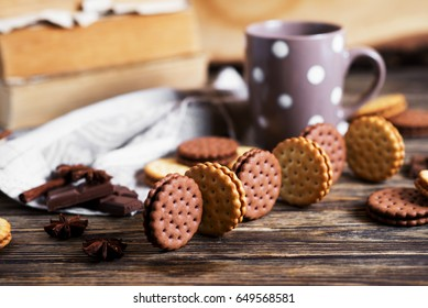 Sweets and desserts, chocolate and milk biscuits sandwich, cracker with cinnamon and tea on a dark wooden rustic background