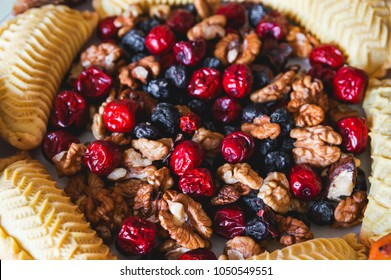 Sweets and desserts for the Novruz holiday on plate - shekerbura, baklava, walnuts and dried fruits