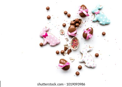 Sweets for Easter table. Chocolate eggs near cookies in shape of Easter bunny on white background top view copy space
