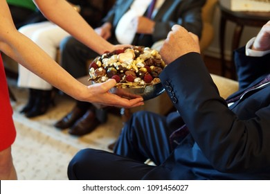 sweets like confectionery and chocolates served by a girl, dressed red, to elder people, a traditional ceremony for ramadan feast of sacrifice feast known as eid al-adha