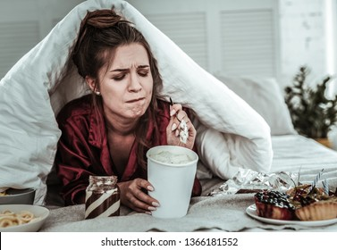 A lot of sweets. A stressed woman covered with a blanket eating a lot of sweets