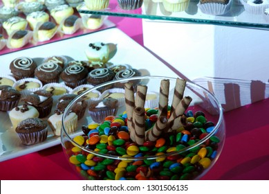 Children's sweets table with close up of a bowl of smarties, chocolate wafers and selection of cup cakes.