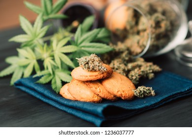 Sweets with weed. Baking with the addition of CBD. Cookies with marijuana. Sweets with cannabis. Cannabis buds on a black background.