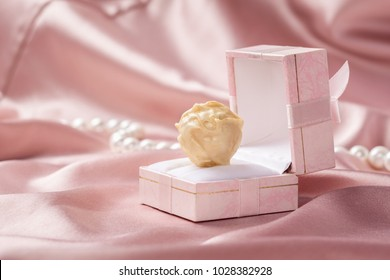 Sweets of white chocolate in a box for jewelry on the background of a delicate satin. Copy space.Holiday concept. Close-up. Selective focus.